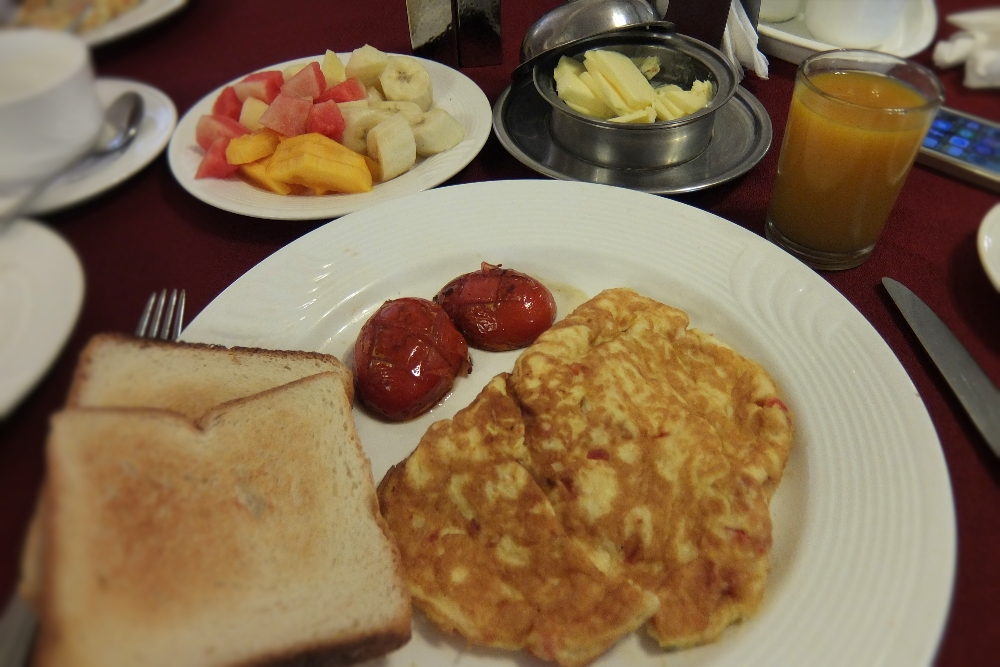Delicious Breakfast at Amar Mahal Hotel in Orchha India which includes omelet, juice, tea and fruits