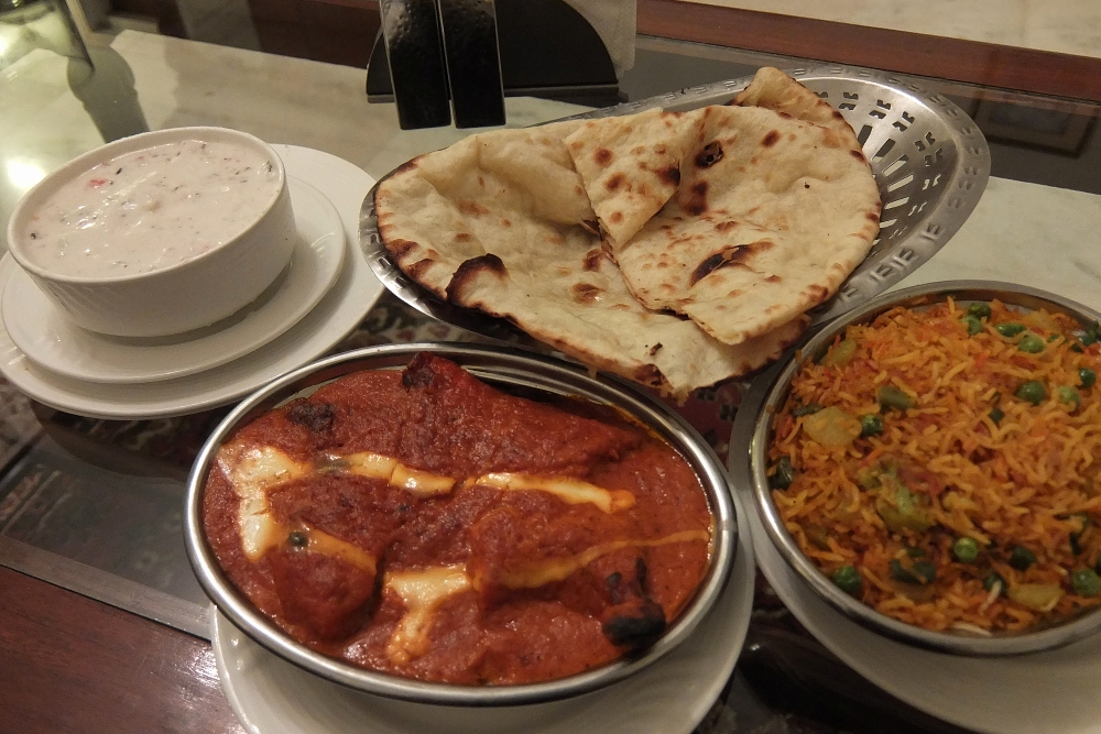 Room Service Meal from Amar Mahal Hotel in Orchha includes Butter Chicken, Cheese Nan, Raita and Saffron Rice
